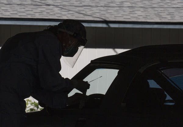 A person wearing PPE and holding a nasal swab in silhouette.
