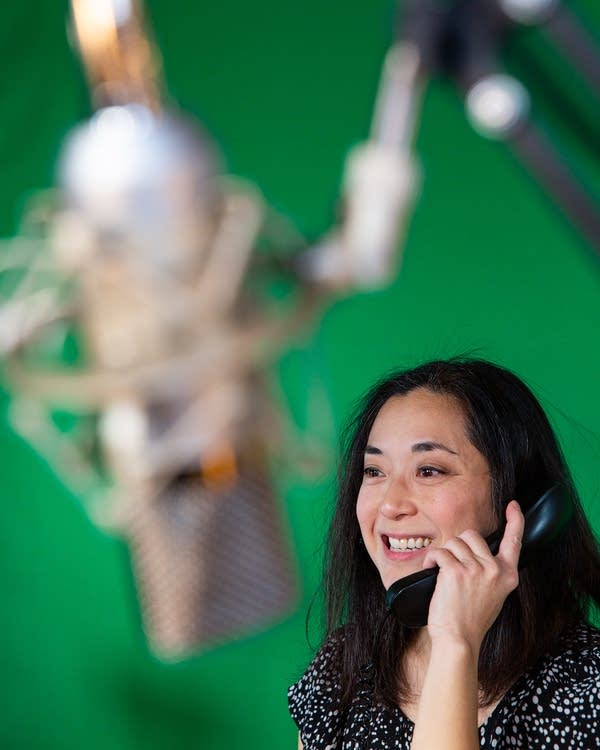 A woman talks into a phone behind a microphone.