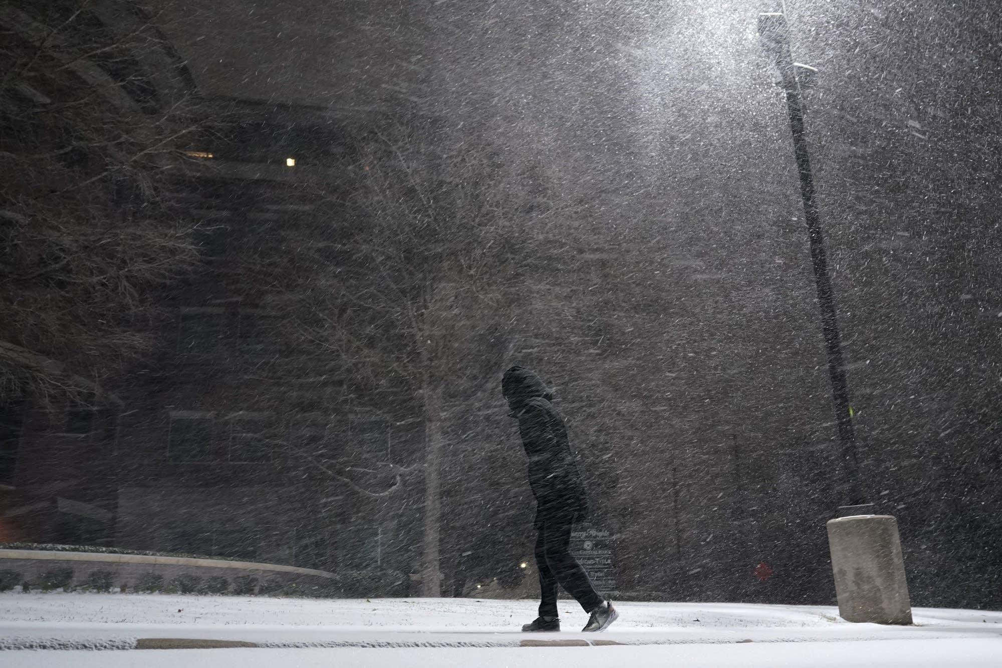 A woman walks through falling snow.
