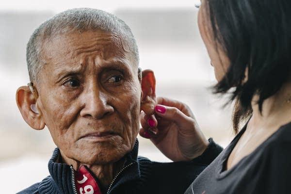 Montha Chum rubs her father Phan Khiev's ear.