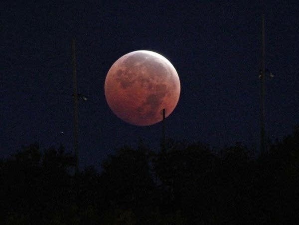 The moon is seen over the Duluth hillside during a lunar eclipse