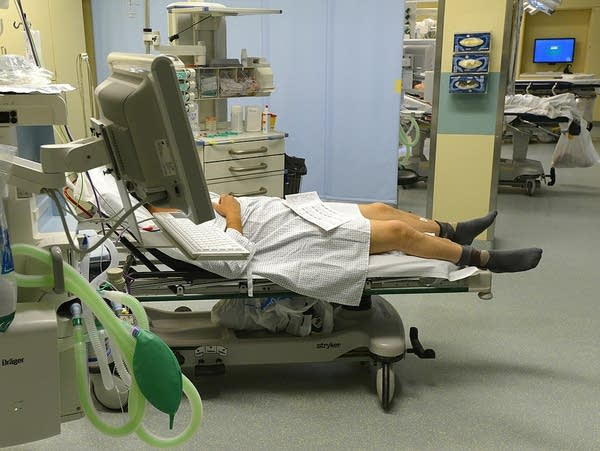 A patient lies in a bed surrounded by medical equipment.