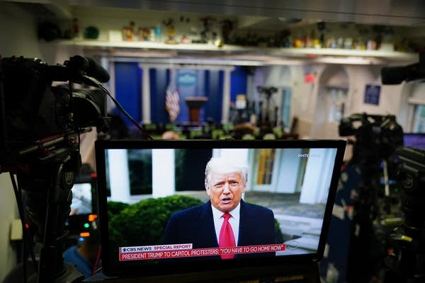 President Donald Trump is seen on TV from a video message.