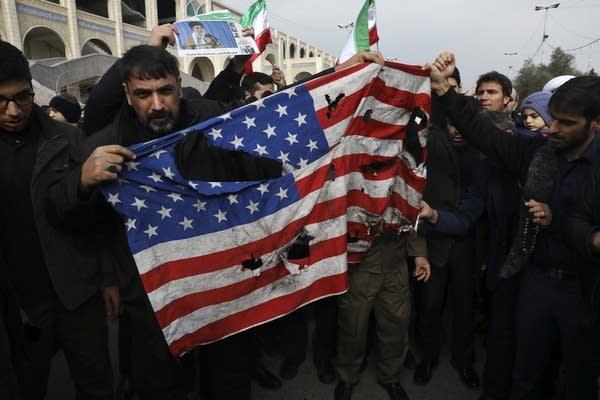 Protesters burn a U.S. flag.