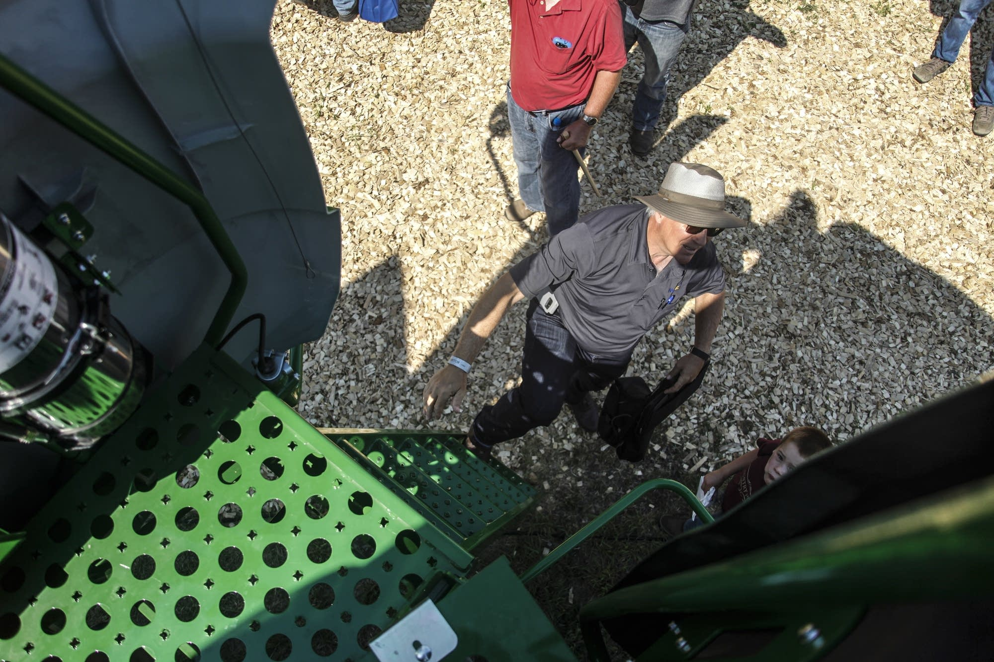 From above, farmers and families try climbing the biggest tractor.