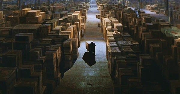 Wide shot of VAST warehouse filled with crates (Raiders of Lost Ark scene)