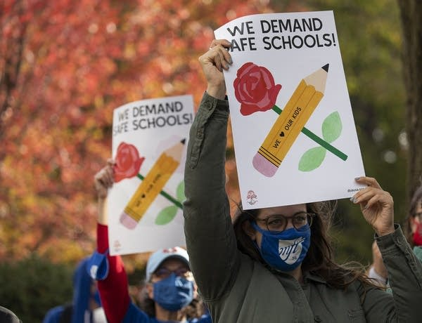 """A person holding a sign that reads """"We demand safe schools"""""""