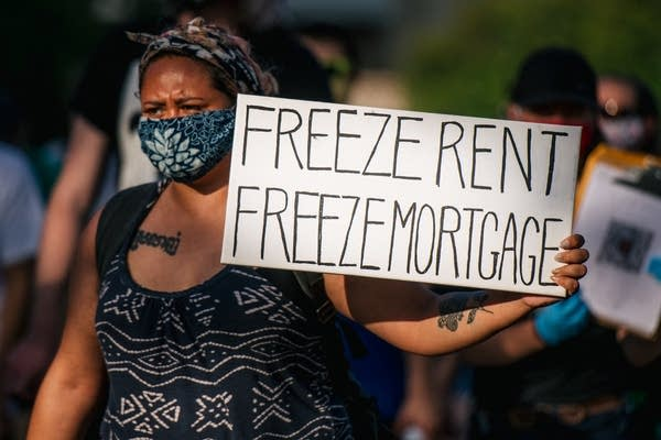 A woman holds a sign up at the the Cancel Rent and Mortgages rally.