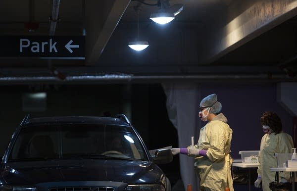 A person wearing a face mask and PPE talks to a person in a car.