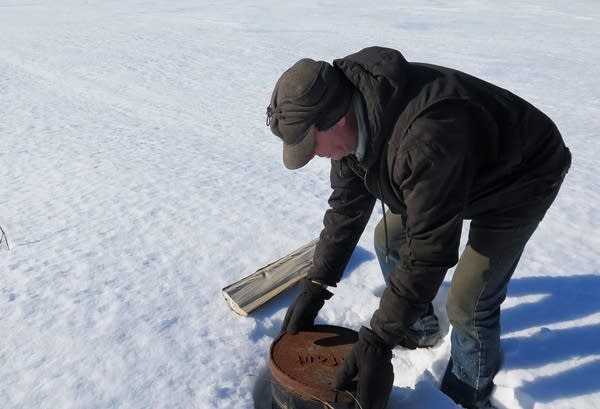 A man checking an irrigation well in a snow-covered field.