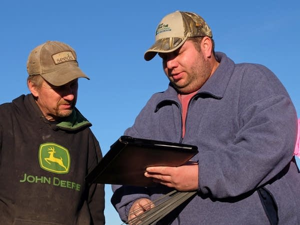 Aaron Larsen, right, shows farmer Don Viger an aerial photo.