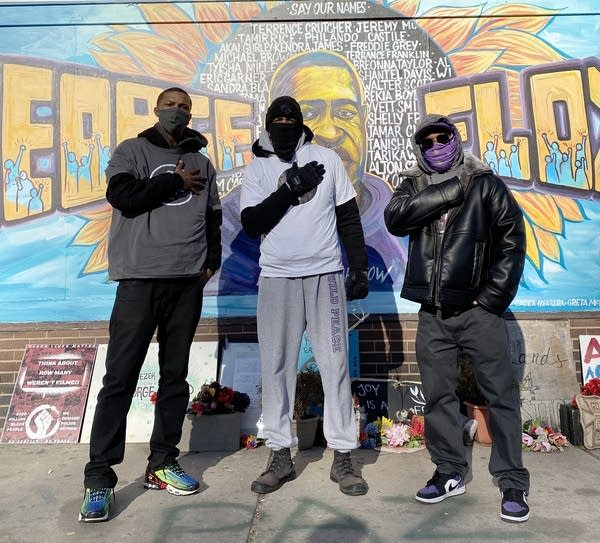 Three men stand in front of a mural.