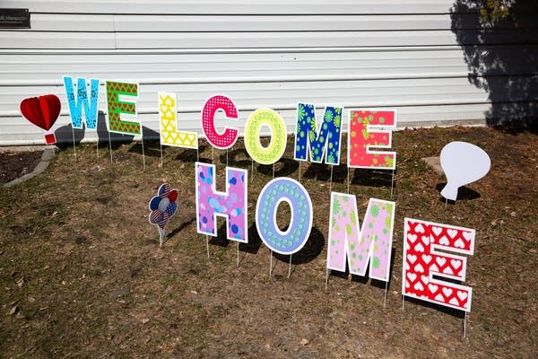 """Signs spell """"welcome home"""" in a yard."""