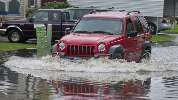 A driver plows through flooded Mankato street.
