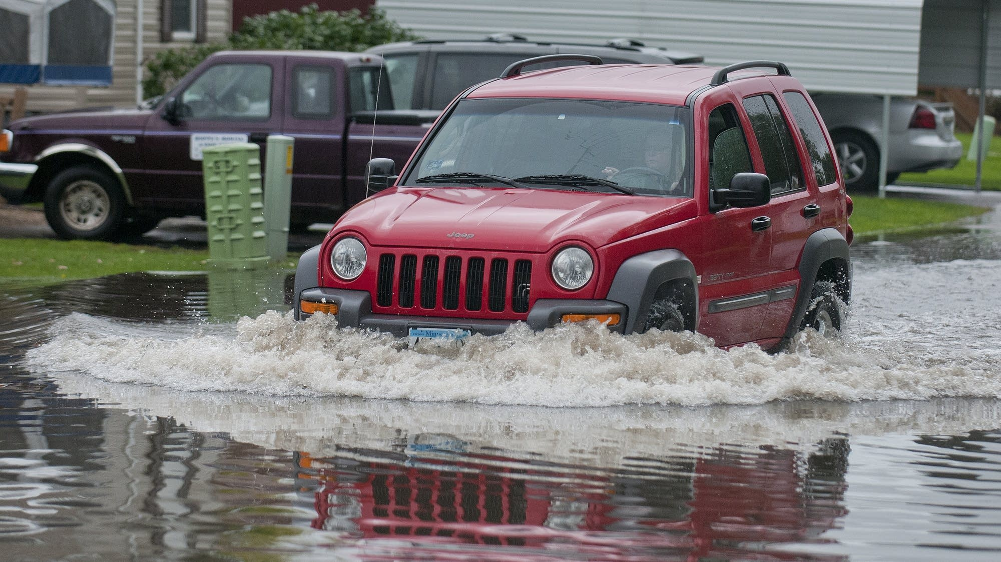 A driver plows through flooded Mankato street.