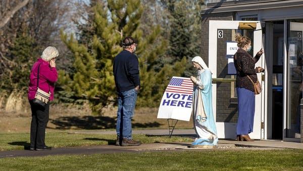 People wait in line outside a church.