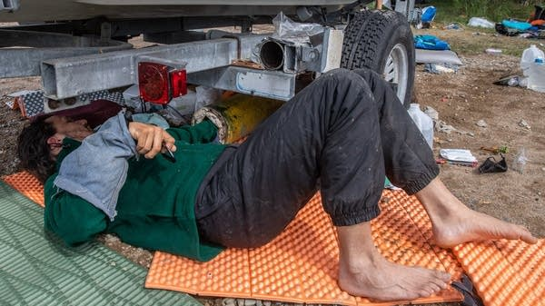 An activist lays on the ground under a boat trailer.