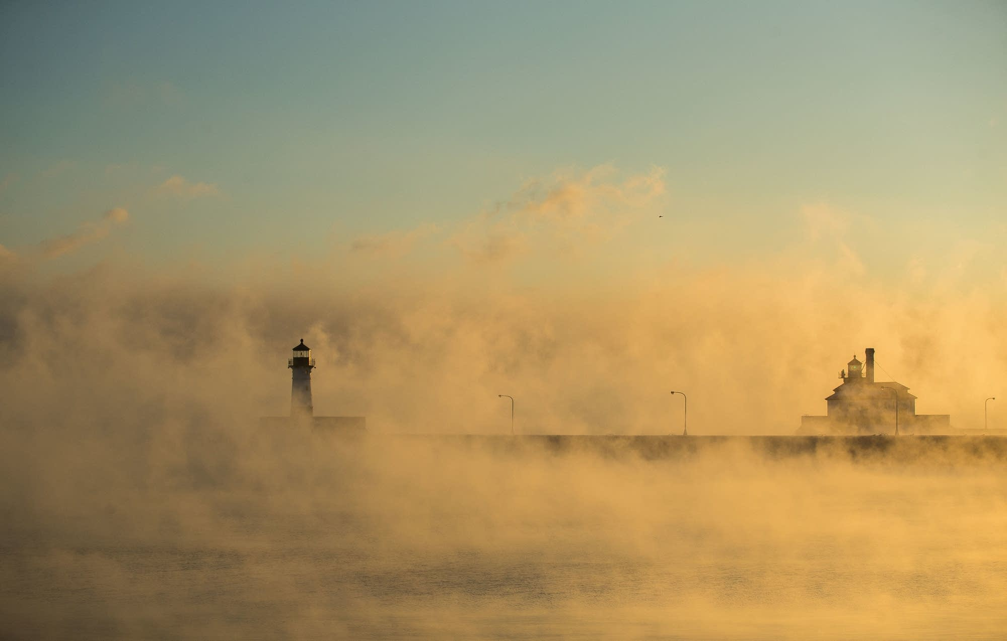 Sea smoke rises over the North Pier and the South Breakwater Outer Lights.