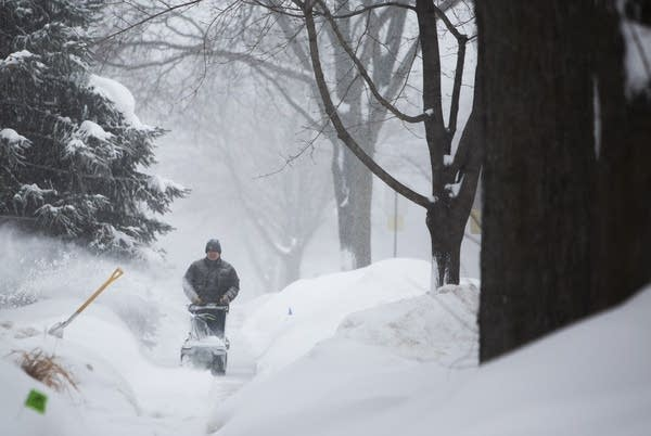 Harry Huie clears snow from the sidewalk in front of his house.