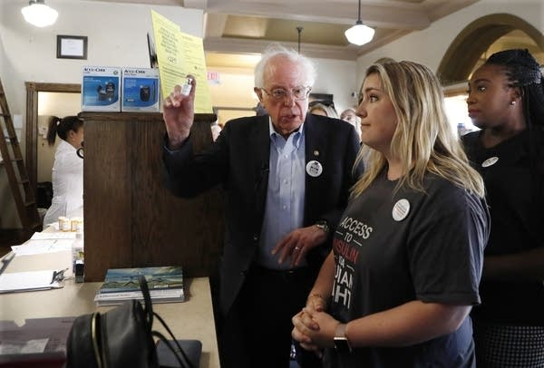 Bernie Sanders holds a vial next to a woman in a pharmacy.