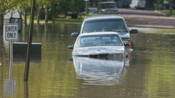 Two cars parked along a flooded street in Waseca.