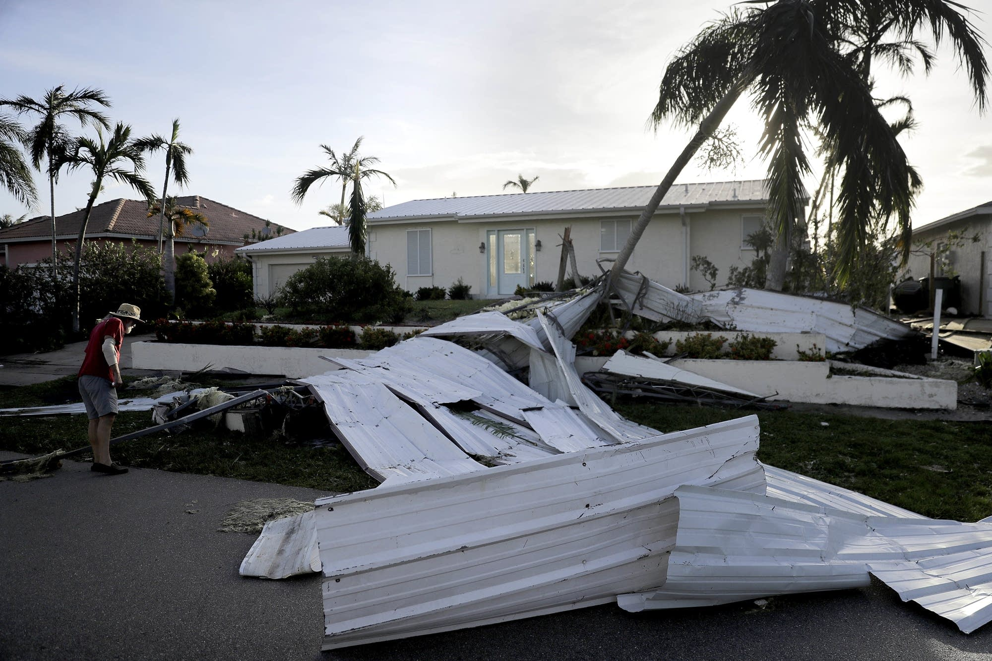 A roof is strewn across a home's lawn.