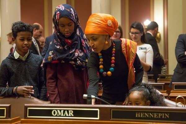Ilhan Omar shows her kids her desk.