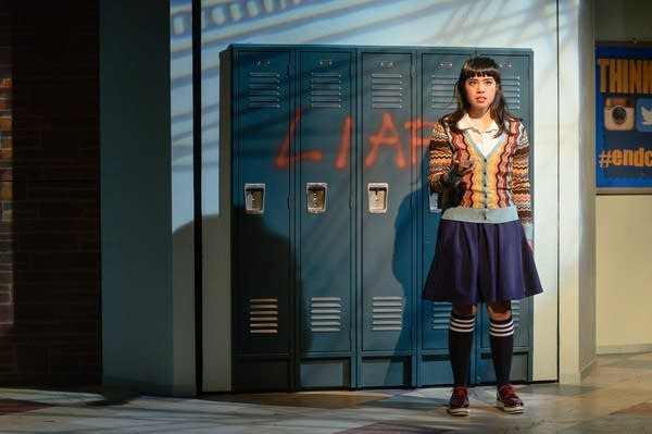Teenage girl standing in front of high school lockers.