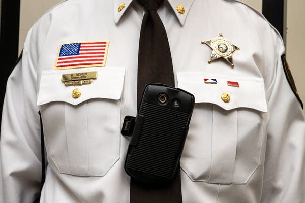 An American flag, badge, tie and body camera on a white shirt.