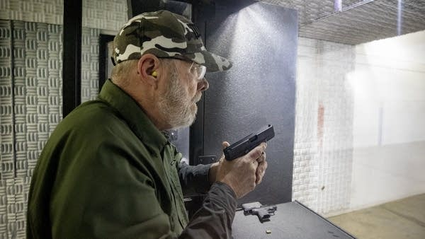A man holding a gun while wearing safety gear at a shooting range.