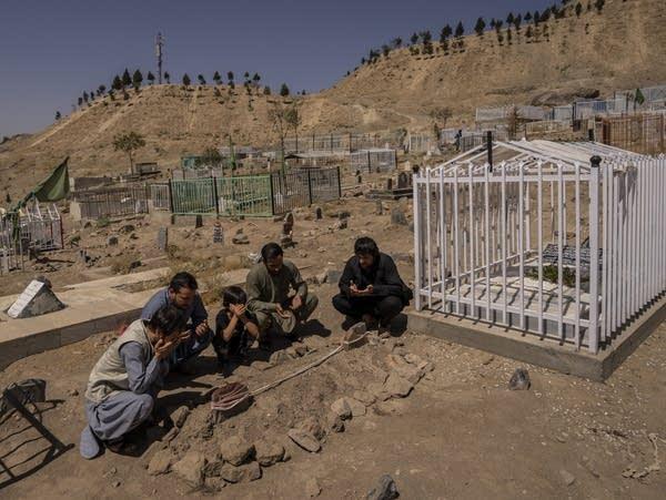 A family prays at a cemetery