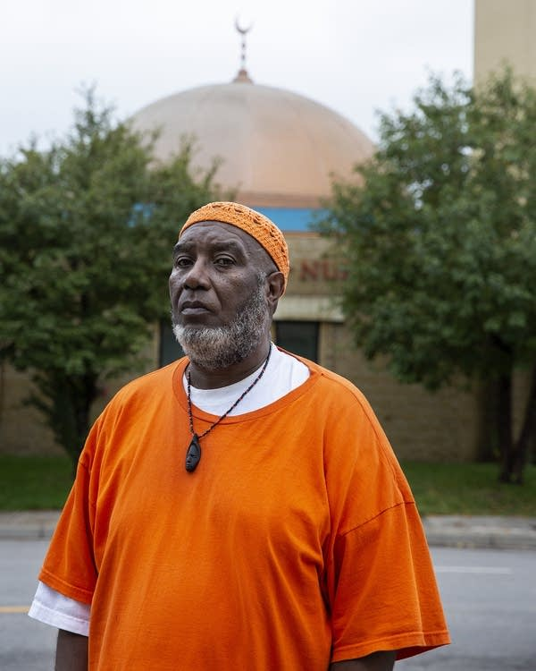 A man wearing an orange shirt and cap stands in front of a mosque.