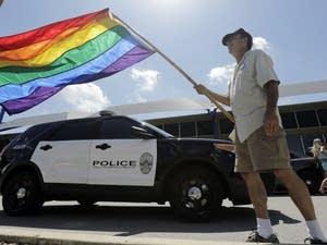Man waves rainbow flag