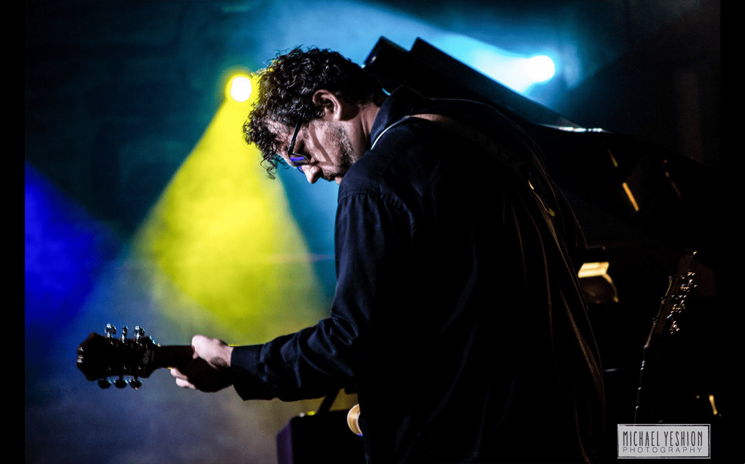 A musician plays a guitar on stage