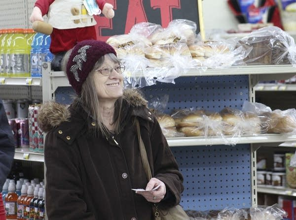 A person smiles as they stand beside a shelf of food.