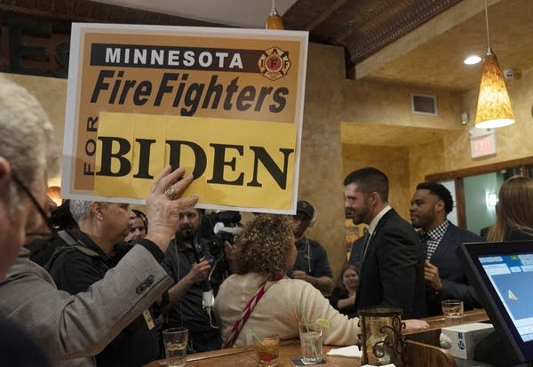 "A person holds a sign that reads ""Minnesota firefighters for Biden"""
