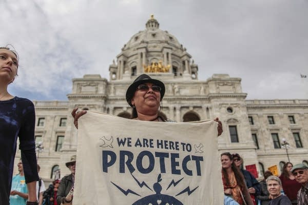 Debra Topping holds a water protect sign in front of the Capitol.