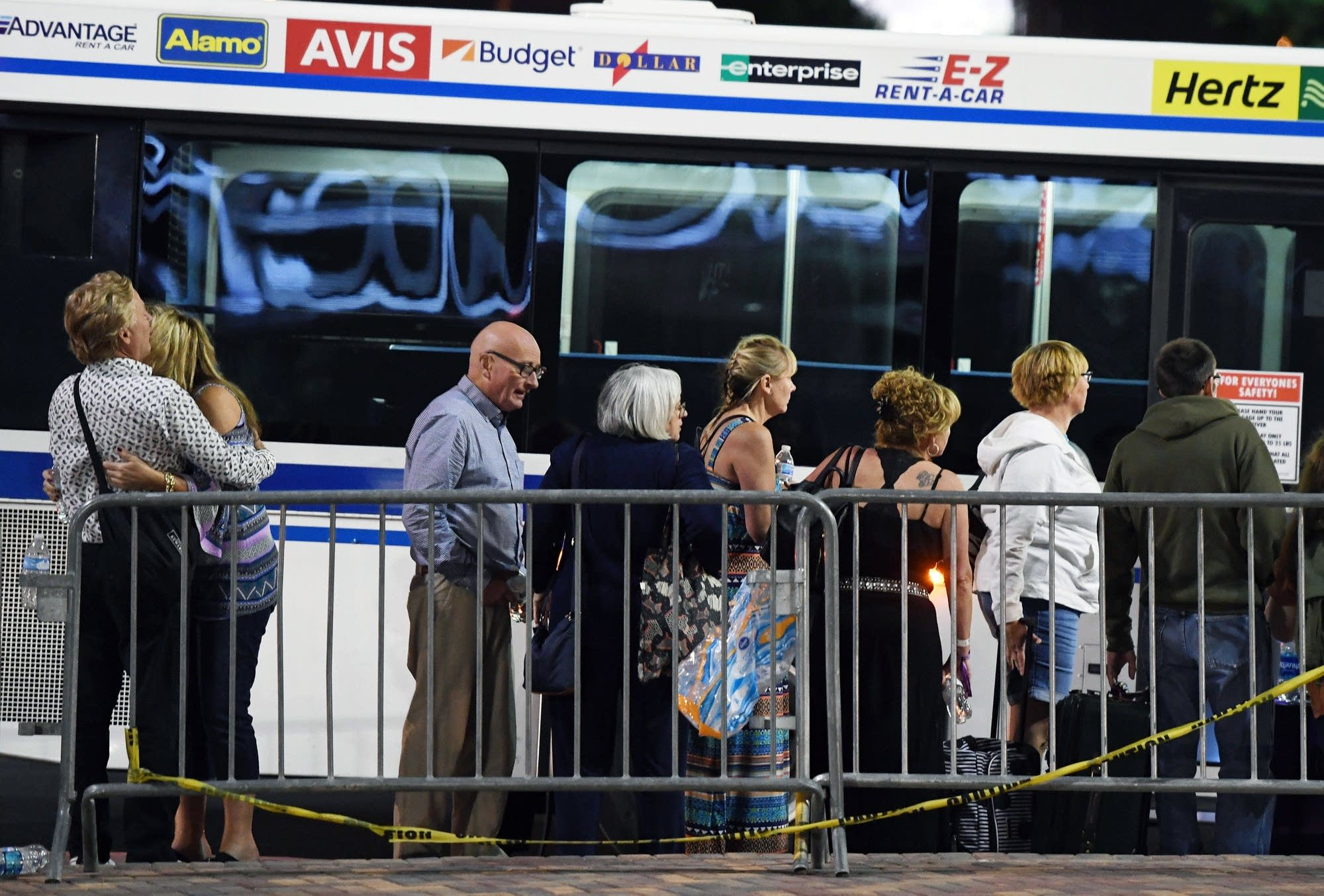 People wait to get on a bus outside the Thomas & Mack Center.