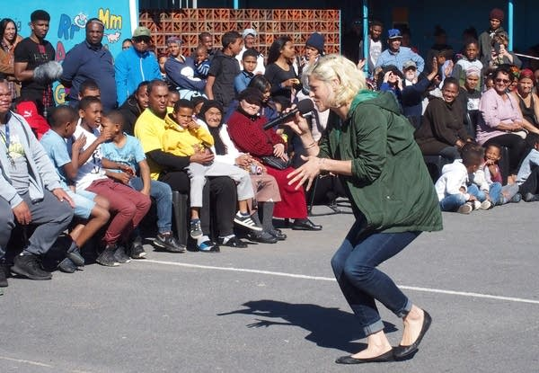 A woman performs in front of a crowd outside.