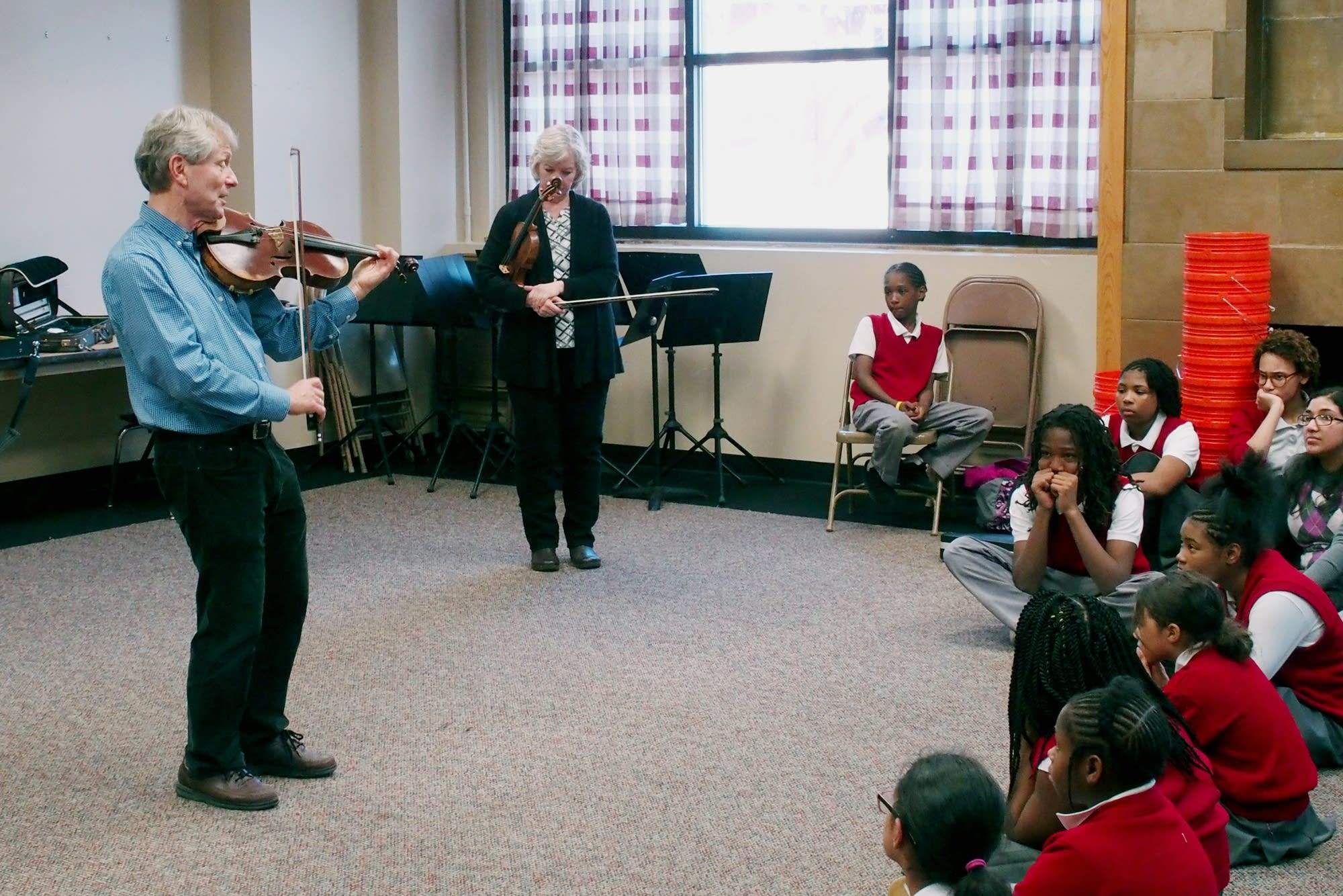 Richard Marshall plays as students from Ascension Catholic School listen