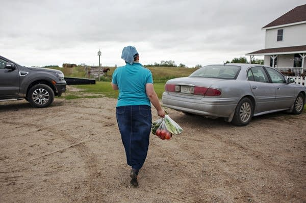 A woman holds a bag of vegetables as she walks to her car.