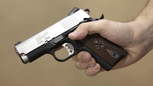 A close up of a hand holding a gun.