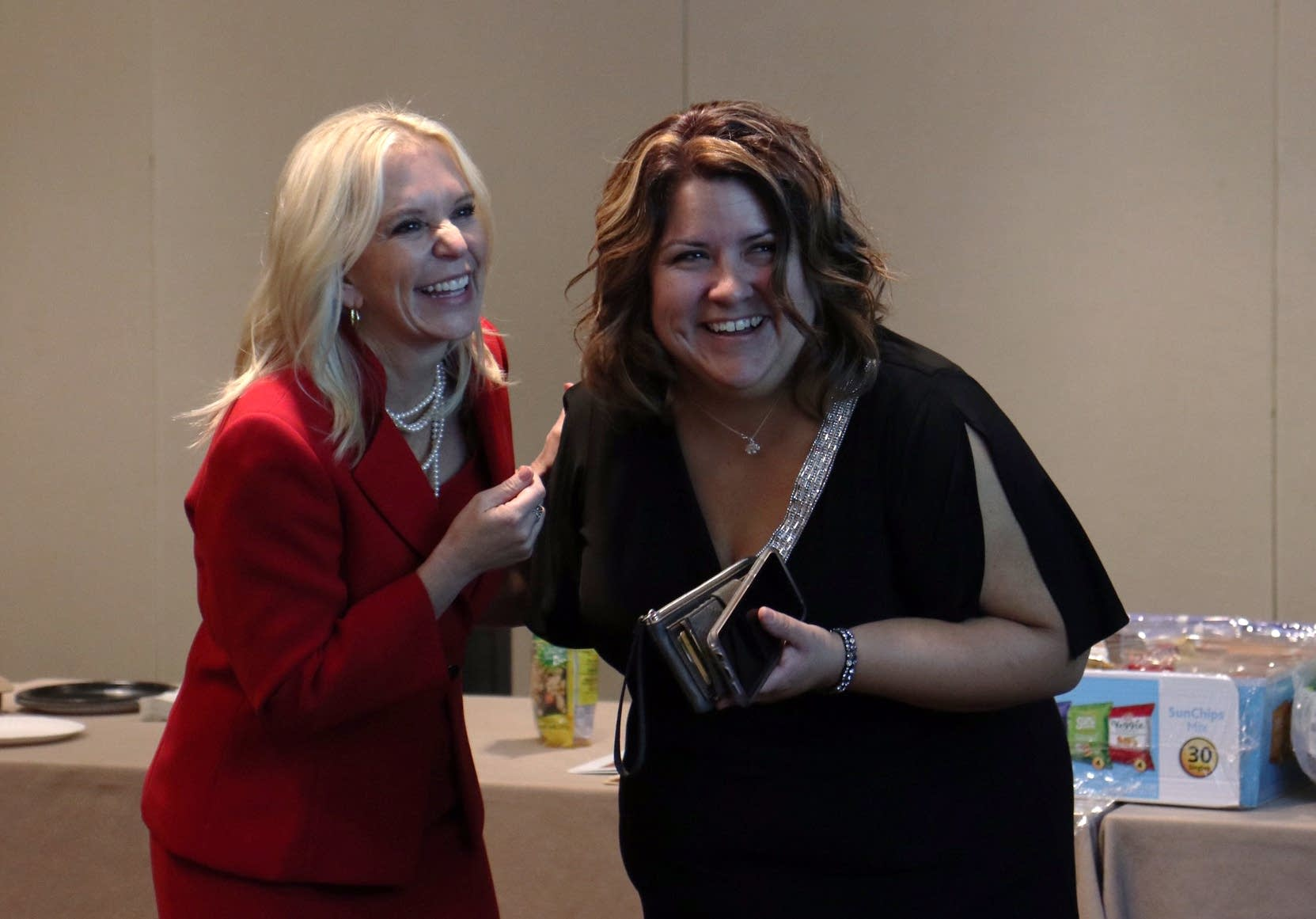 Karin Housley and her finance director laugh as they look at numbers.