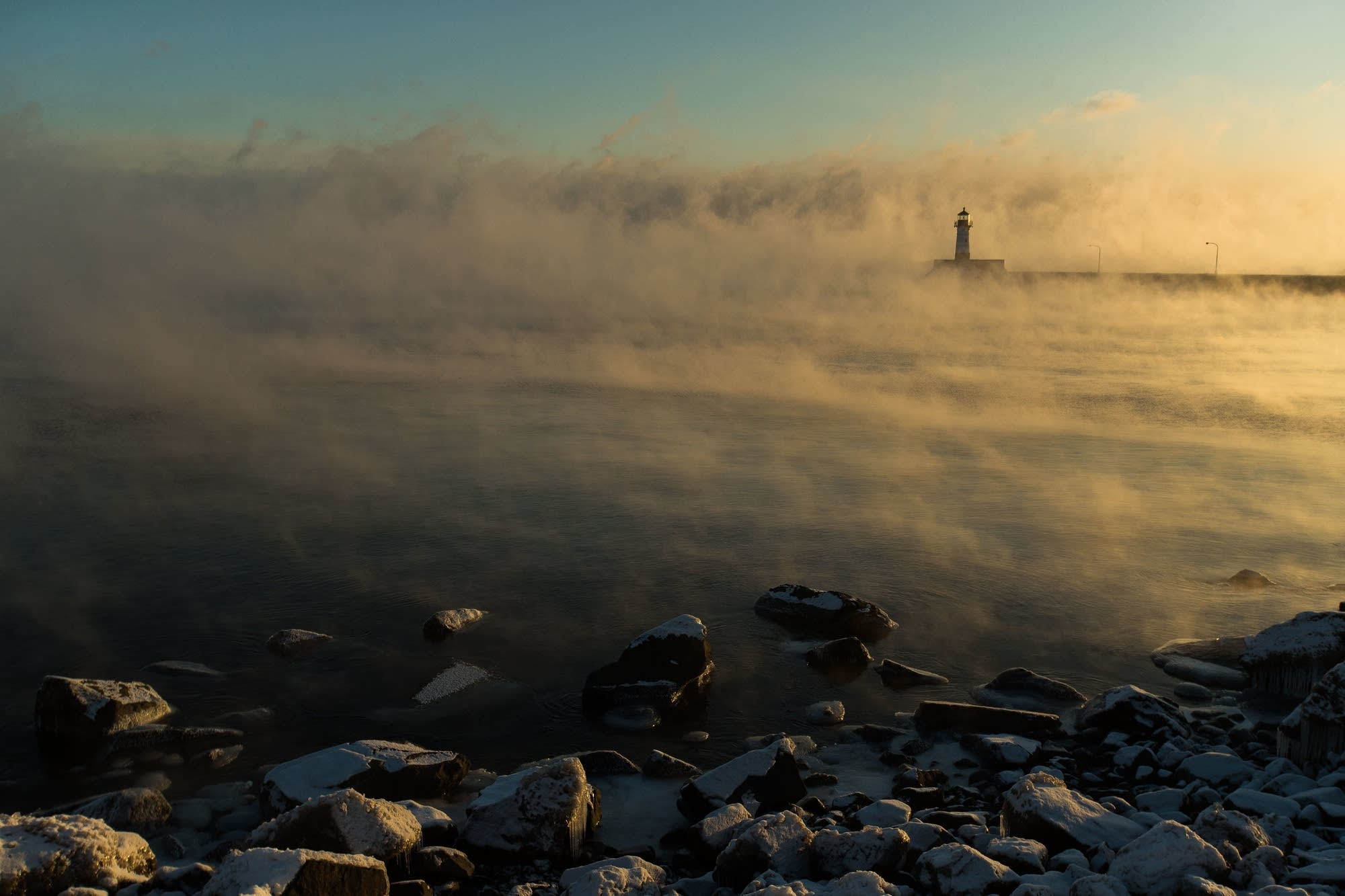 Sunlight shrouds and sea smoke rises over the North Pier Light.