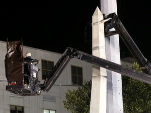 Workers dismantle the Liberty Place monument