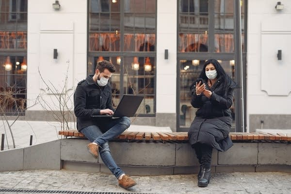 Two people with masks on sit on a bench outside