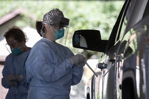 A person wearing PPE holds a swab while standing beside a truck.