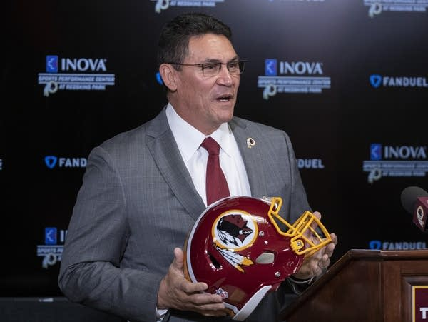 A man in a suit holds a football helmet.