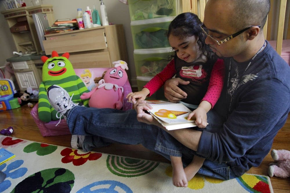 Christopher Astacio reads to his daughter