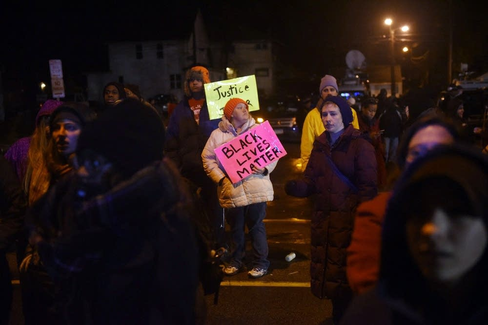 Protesters stand outside the precinct.